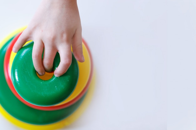 Ребенок собирает пирамиду. детали игрушки в руках.