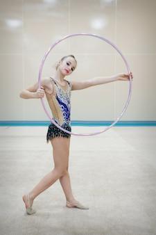 Девушка в спортивном костюме делает обруч с обручем. концепция здорового образа жизни, спортивная форма, чемпионат мира, тренажерный зал, спецодежда, униформа