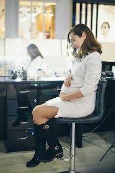 妊婦がおなかを撫でている。