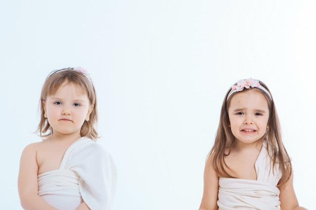 少女は白い背景にしかめっ面。子供たちは何かをしている。感情、表情、子供時代、誠実さの概念