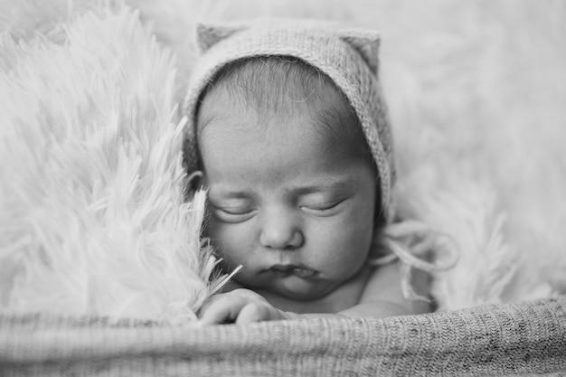 耳付きニット帽子の生まれたばかりの赤ちゃん。子宮の中で赤ちゃんの模倣。新生児の肖像..健康、子育て、子供の日、医学、体外受精、ファッションの概念