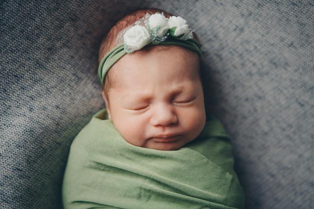 彼の頭のクローズアップに花と包帯を持つ子供の顔