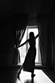ウィンドウで踊っている女の子のシルエット。光の中の女性。女性の身体、優雅さ、スポーツ、美しさ、スタイルを強化するコンセプト
