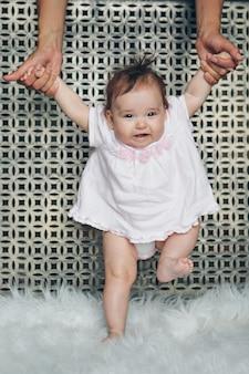 かわいい赤ちゃんが歩き始め、最初の一歩を踏み出すことを学ぶ。お母さんは彼の手を握っています。子供の足をクローズアップ、コピースペース