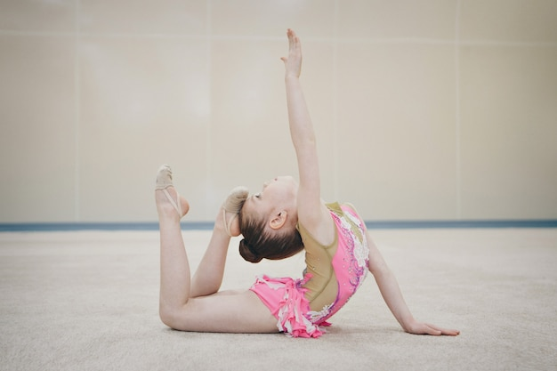 Девушка в спортивном костюме делает растяжку. гимнастка занимается спортом. концепция здорового образа жизни, спортивная форма, чемпионат мира, тренажерный зал, спецодежда, униформа