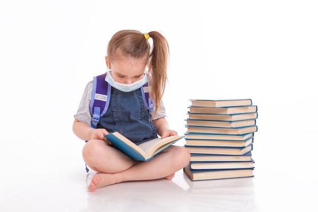一年生は読むことを学ぶ。家庭用遠隔学習の小さな女の子。医療用マスクをした子供が本を読みます。