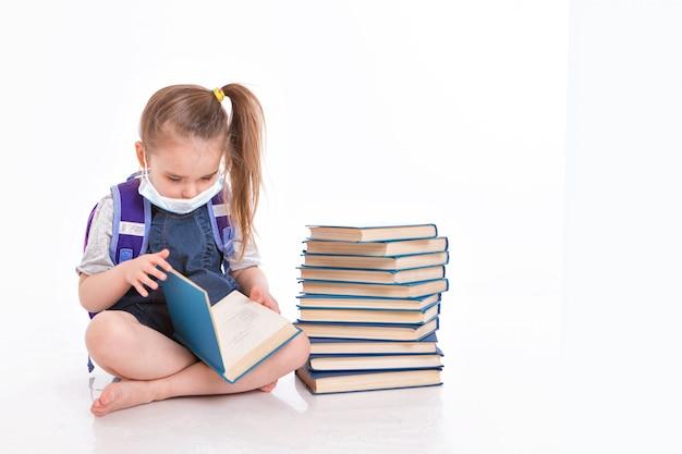 Первоклассник учится читать. маленькая девочка на дому дистанционного обучения. ребенок в медицинской маске читает книгу.