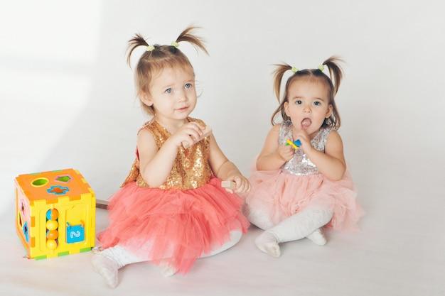 Две маленькие девочки играют на полу на белом фоне