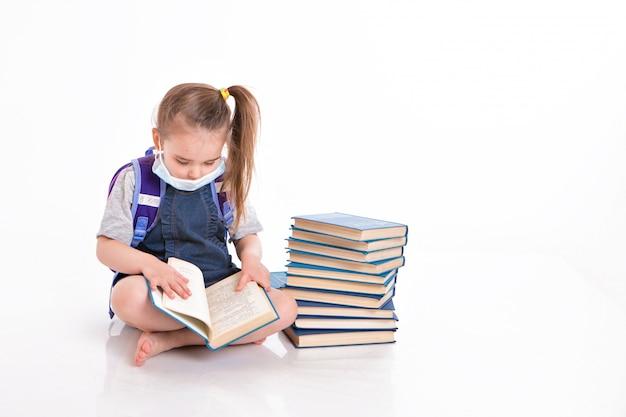 Первоклассник учится читать. маленькая девочка на домашнем дистанционном обучении. ребенок в медицинской маске читает книгу. студент делает домашнее задание.
