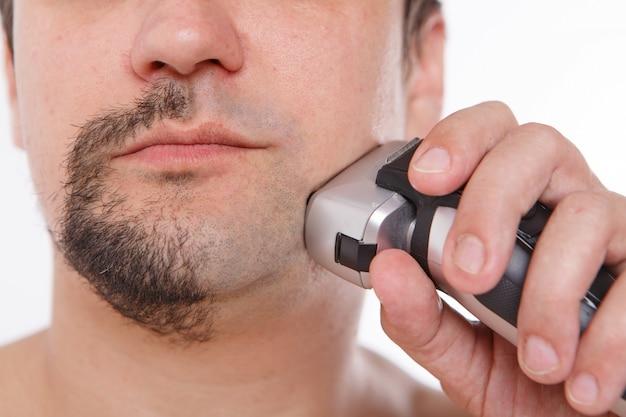 Человек бреет щетину парень чистит бороду электрической бритвой. утренние процедуры в ванной.