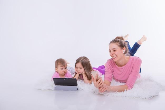 日常生活の現代技術:女性はヘッドセットを介して電話で話し、子供たちはタブレットで漫画を見る。