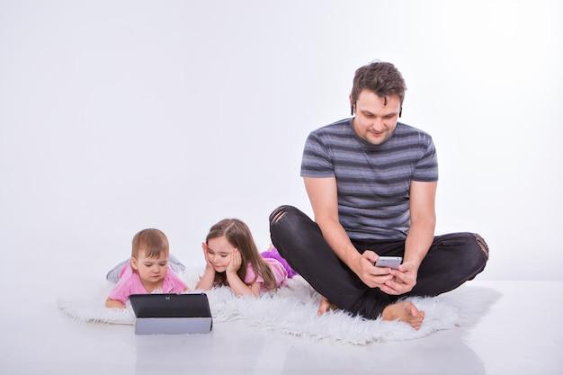 日常生活の現代技術:男はヘッドセットを介して電話で話し、子供たちはタブレットで漫画を見る。