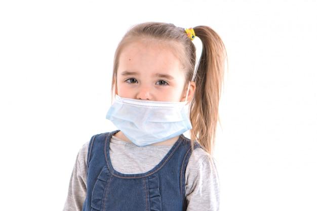 白い背景の上のフェイスマスクを着ている少女。