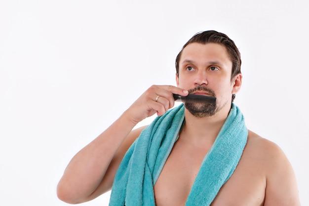 男が無精ひげをとかします。男はひげを磨いています。バスルームでの朝のトリートメント。彼女の首に青いタオル。白い背景で隔離されました。コピースペース