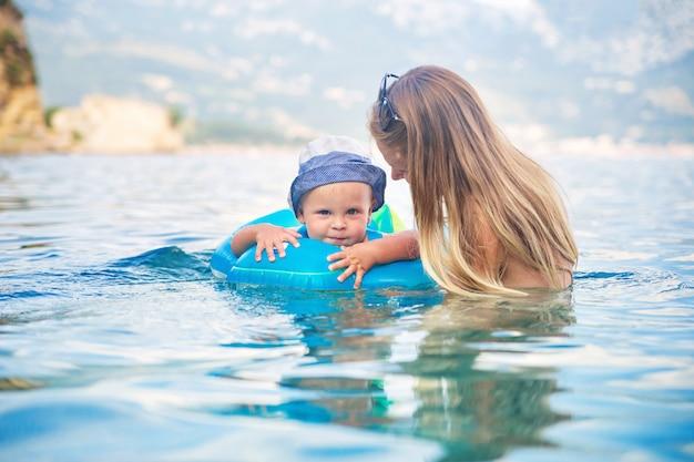 彼の母親と一緒に幸せな子供がアドリア海の水泳リングで泳ぐ
