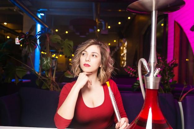 赤いドレスの若い女性は、水ギセルバーで水ギセルを吸います。