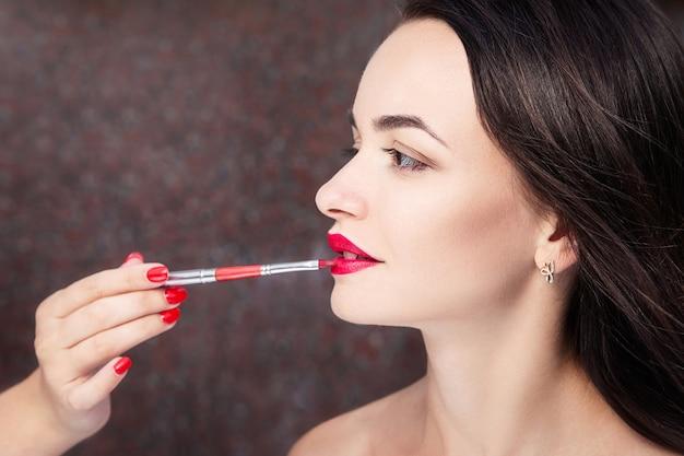 メイクアップアーティストは、美しい若い女性に化粧をします