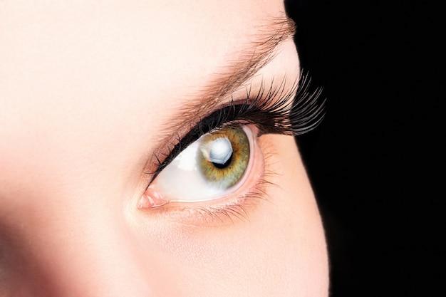 長いまつげと女性の緑色の目。まつげエクステンション、ラミネーション、美容、眼科。良好な視力、透明な肌