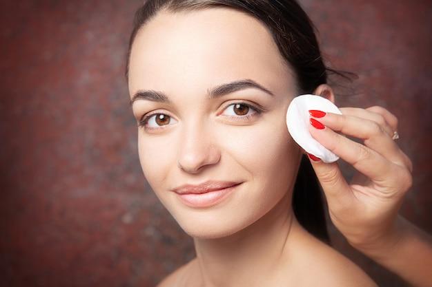 Косметолог снимает макияж с лица молодой красивой женщины, портрет крупным планом на красном фоне