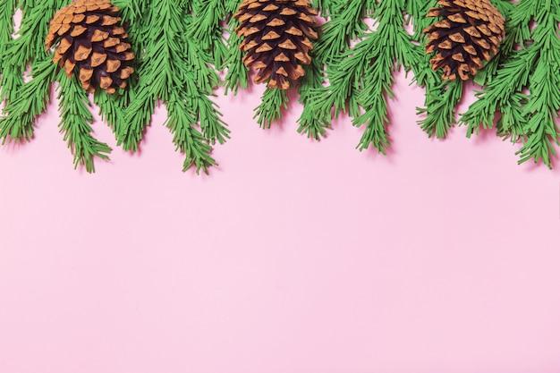 ピンクの背景のフラットコーンと緑の泡クリスマスツリーブランチの境界線を置く