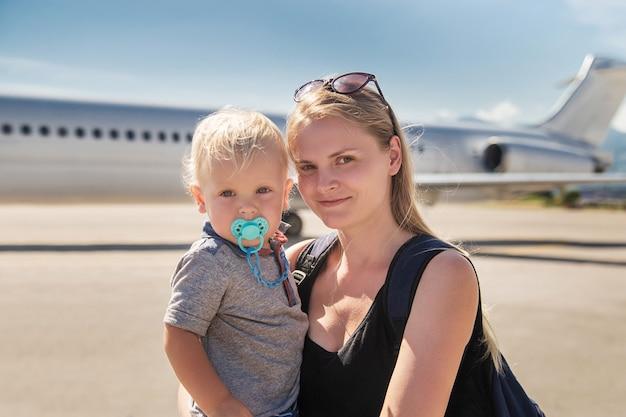 飛行機の中で彼女の子供を保持している若い母親。空港でのコーカサス地方の家族。旅行、赤ちゃんと一緒に飛行、観光の概念