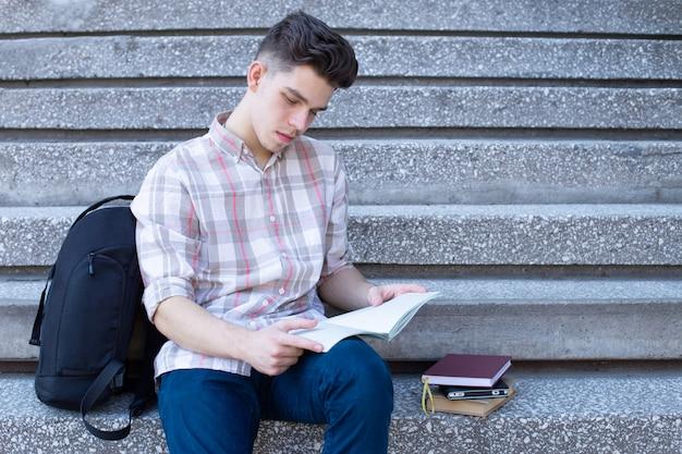 Молодой парень студент сидит на лестнице школы