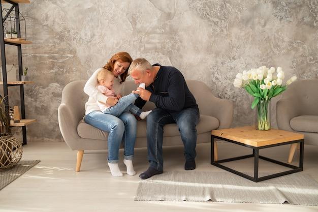 女の赤ちゃんとソファに座って幸せな家族。祖父と祖母は、屋内の孫娘と一緒に一日を過ごします