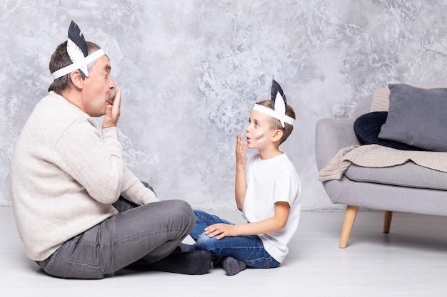 白人の少年と彼の祖父は灰色の壁の壁でインディアンを演じます。年配の男性と孫がリビングルームで遊ぶ