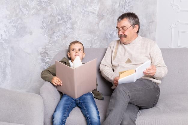 祖父と孫は、リビングルームで一緒に本を読んで座っています。少年と彼の笑顔のおじいちゃんは、屋内で一緒に時間を過ごします。子供を持つ年配の男性