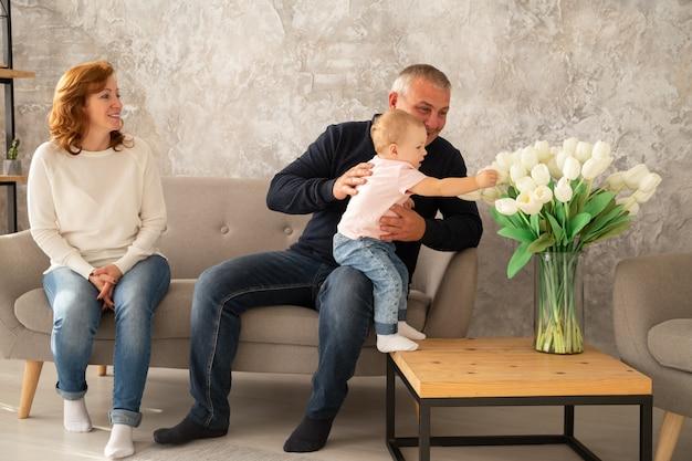 女の赤ちゃんとソファに座って幸せな家族。祖父と祖母は家族の家で孫娘と一緒に一日を過ごします