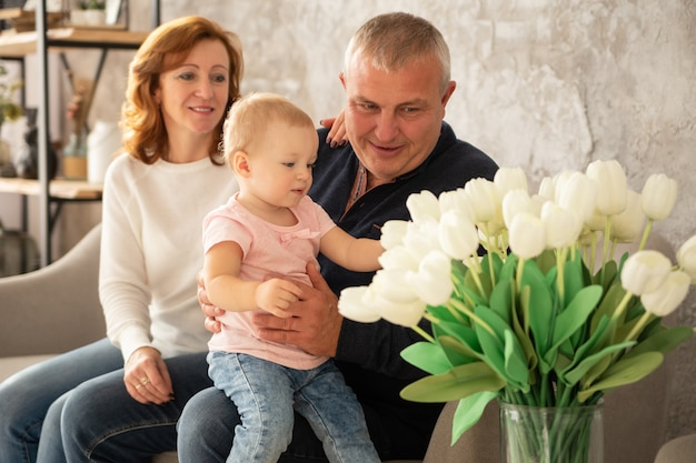 甘い女の赤ちゃんとソファに座って幸せな家族。祖父と祖母は、屋内の孫娘と一緒に一日を過ごします