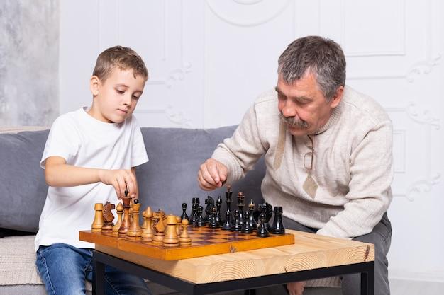 祖父は孫と屋内で古いチェスをしています。少年と彼のおじいちゃんは、リビングルームのソファに座って遊んでいます。年配の男性は子供にチェスをすることを教える