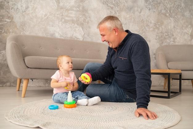 小さな女の赤ちゃんは、リビングルームで祖父母とピラミッドを収集します。祖父はソファの近くの床で孫娘と遊ぶ