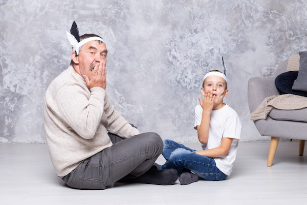 少年と祖父は灰色の壁にインディアンを演じます。年配の男性と孫はリビングルームでインディアンを再生します。家族一緒に
