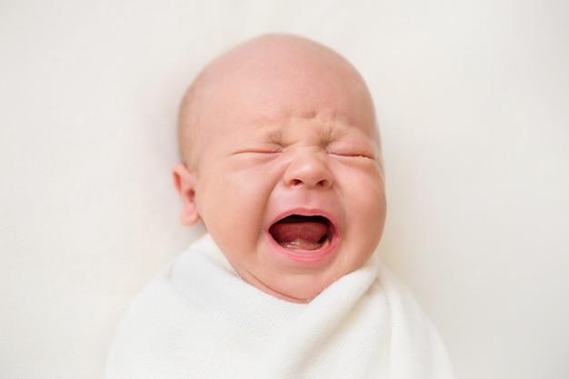 白い背景の上の生まれたばかりの赤ちゃんの男の子。赤ちゃんが泣いている
