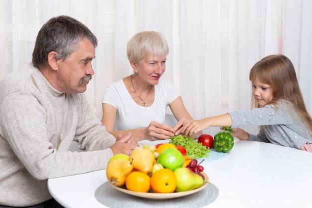 孫娘と祖父母は、キッチンで健康食品を準備します。家族一緒にサラダを準備します
