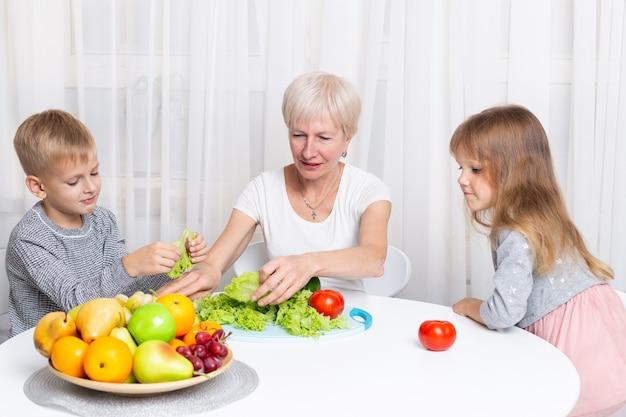 孫娘と孫と祖母は、キッチンで健康食品を準備します。家族一緒にサラダを準備します