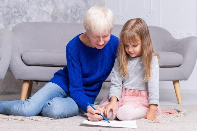 祖母と孫娘が一緒にリビングルームの床にペイントします。大人の女性は女の子が絵を描くのを手伝います