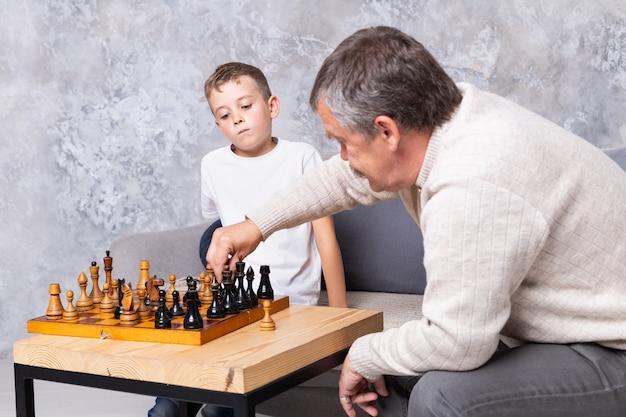祖父は孫と古いチェスをしています。少年と彼のおじいちゃんは、リビングルームのソファに座って遊んでいます。年配の男性は子供にチェスをすることを教える