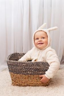 Улыбающийся маленький мальчик в костюме кролика пасхи, сидя в корзине у себя дома