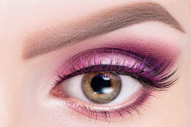 ピンクバイオレットの影とつけまつげの女性の目
