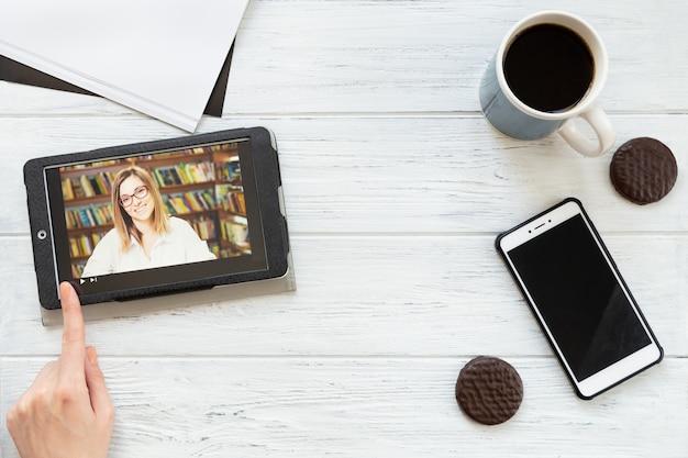 タブレット、電話、コーヒー、クッキーを備えたデスクトップ、フラットレイアウト。オンライン学校、仮想教育
