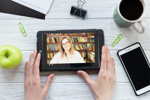 タブレット、電話、コーヒー、アップル、トップビューのデスクトップ。女性が教育用ビデオを見ている