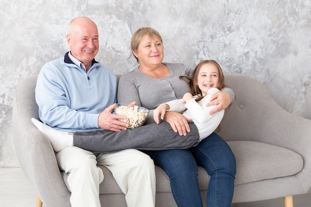Бабушка и дедушка вместе с внучкой смотрят телевизор, кино в помещении