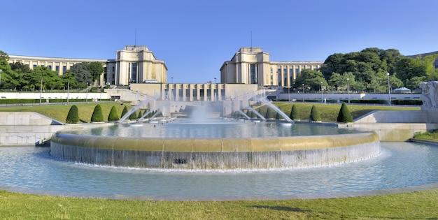 パリのシャイヨー宮殿の背景とトロカデロ庭園の噴水を表示します。