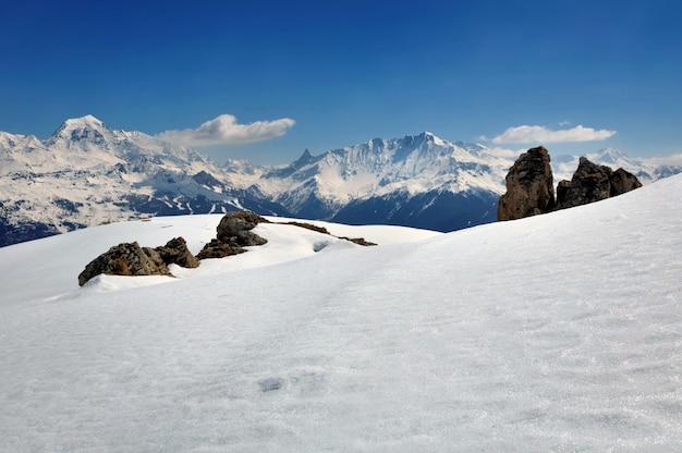 冬の青い空の下で山を雪します。