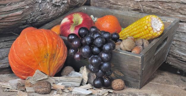 Фрукты и овощи в коробке на деревянном фоне