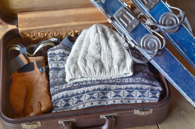 古いスキーは暖かい服を着たスーツケースに反する