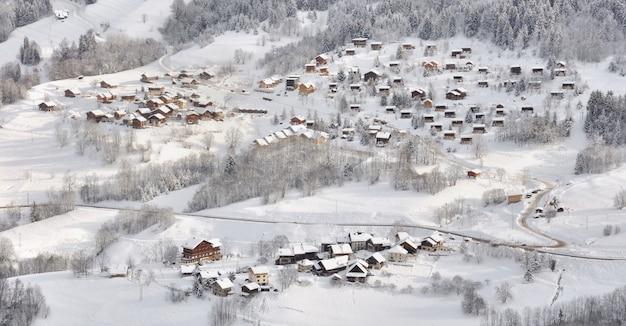 Дома в альпийской деревне в горах, покрытых снегом