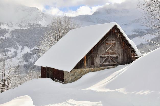 降雪後雪で覆われた山の木造シャレー
